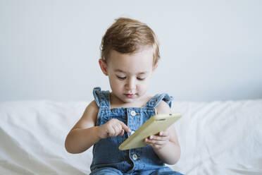 Baby girl using smartphone on bed - EBBF00329