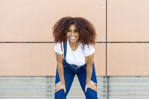 Smiling young woman with afro hair standing against wall in city - JSMF01561