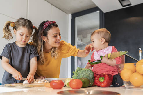 Mother playing with daughter while girl cutting vegetables on kitchen island - JAF00023