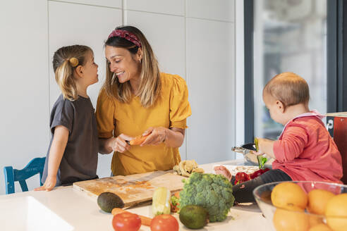 Smiling mother and girl preparing food while baby daughter playing on kitchen island - JAF00026