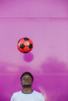 Young man juggling with soccer ball against pink wall in city - LJF01679