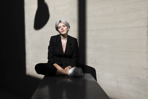 Stylish female professional wearing elegant black suit sitting against wall in office - TCEF00826