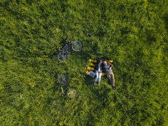 Aerial view of young couple at the green lawn, Tikhvin, Russia - KNTF04730