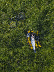 Aerial view of young woman at the green lawn, Tikhvin, Russia - KNTF04736