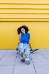 Smiling young woman sitting on skateboard in front of yellow wall - TCEF00855