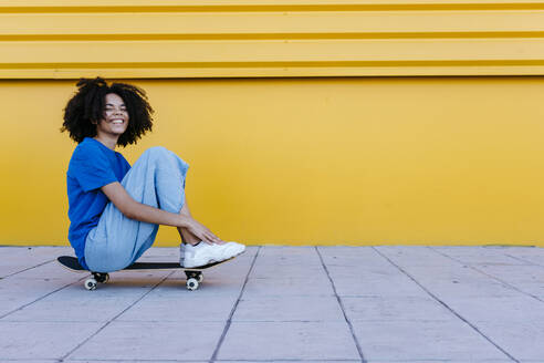 Smiling young woman sitting on skateboard in front of yellow wall - TCEF00858