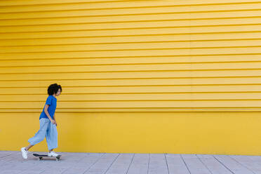Young woman skateboarding in front of yellow wall - TCEF00861