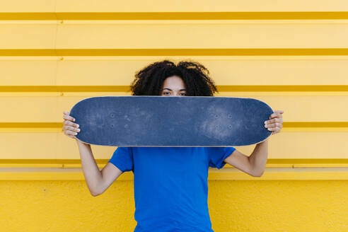 Young woman holding skateboard in front of face, looking at camera - TCEF00864