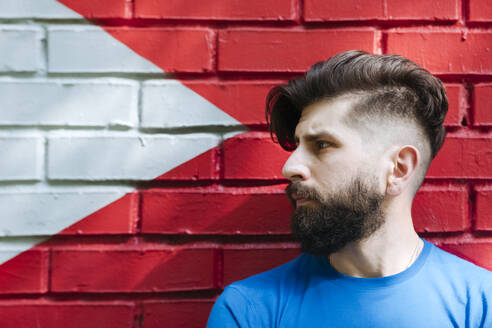 Young man with tattoo standing in front of red brick wall, portrait - EYAF01203