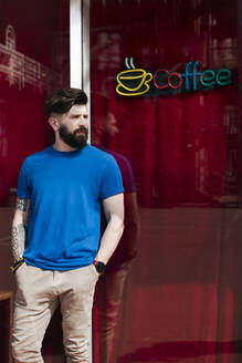 Young man leaning on windowpane of coffee shop - EYAF01209
