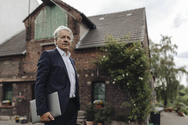 Portrait of a senior businessman holding laptop in front of a farmhouse - GUSF04021