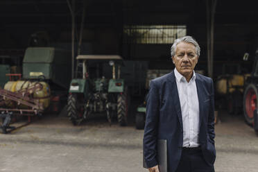 Portrait of a senior businessman on a farm with tractor in barn - GUSF04036