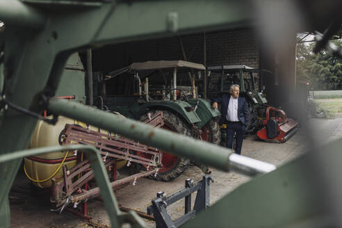 Senior businessman on a farm with tractor in barn - GUSF04039
