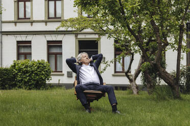 Relaxed senior businessman sitting on a chair in a rural garden looking up - GUSF04045