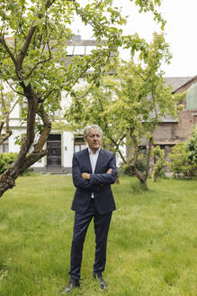 Confident senior businessman standing in a rural garden - GUSF04051