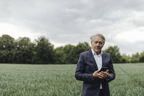 Portrait of senior businessman holding smartphone on a field in the countryside - GUSF04063