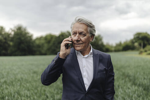 Senior businessman on the phone on a field in the countryside - GUSF04066