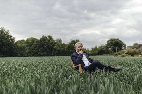 Senior businessman sitting on a chair in a field in the countryside - GUSF04069