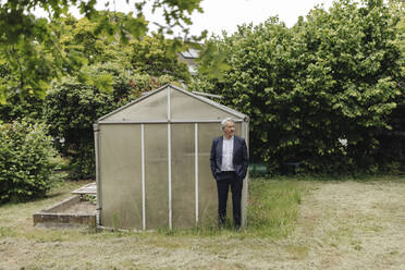 Senior businessman standing at a greenhouse - GUSF04072