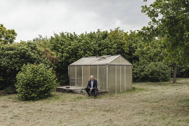 Senior businessman sitting at a greenhouse - GUSF04075