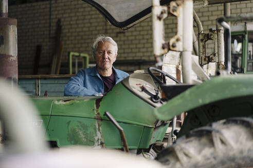 Portrait of a senior man on a farm with tractor in barn - GUSF04120