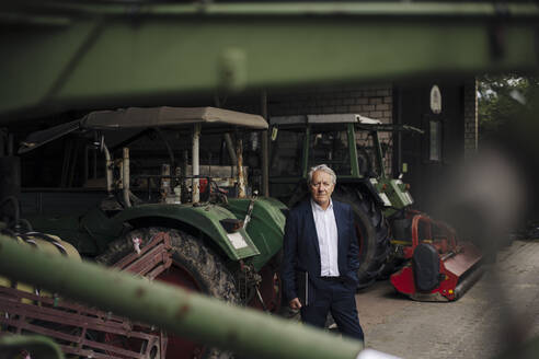 Senior businessman holding laptop on a farm with tractors in barn - GUSF04138
