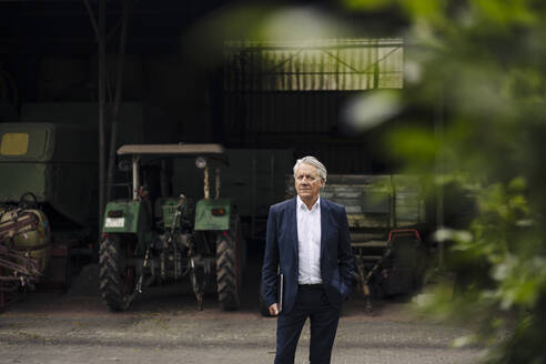 Portrait of senior businessman holding laptop on a farm with tractor in barn - GUSF04141