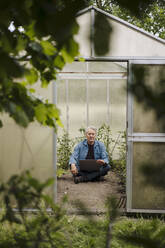 Senior man sitting in a greenhouse using laptop - GUSF04177