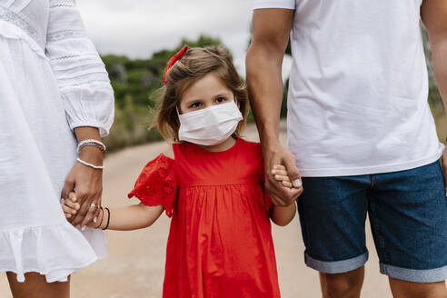 Girl wearing mask while holding hands of parents on country road - EGAF00354