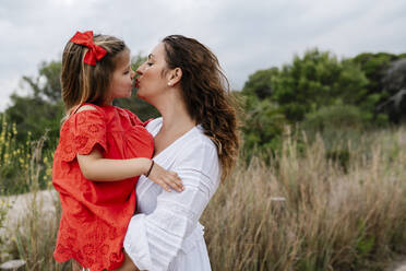 Affectionate mother and daughter kissing at countryside - EGAF00363