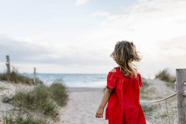 Girl walking at beach against cloudy sky - EGAF00381