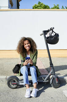Happy young woman holding smart phone while sitting on sidewalk with electric push scooter - KIJF03138