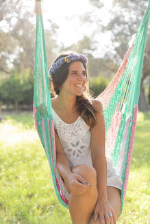 Happy young woman wearing wreath while sitting in hammock at yard - LVVF00137