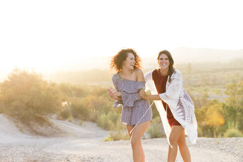 Cheerful female friends walking at countryside against clear sky - LVVF00161