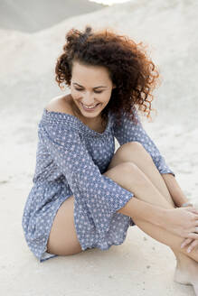 Happy young woman sitting on sand at countryside - LVVF00170