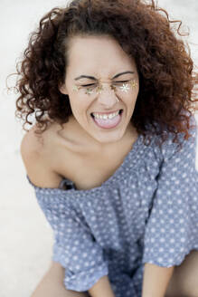 Playful young woman with confetti stuck on face during sunny day - LVVF00173