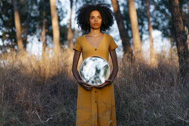 Young woman with afro hair holding mirror while standing in forest at sunset - TCEF00879