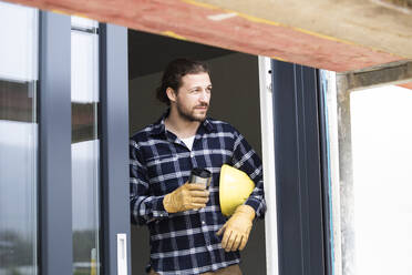 Male worker holding container while standing in house at construction site seen through window - MJFKF00398