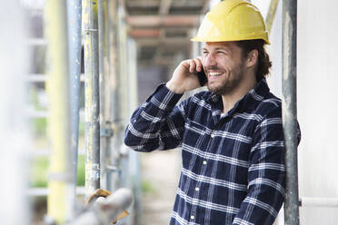 Construction worker talking over smart phone while standing by scaffold at construction site - MJFKF00404