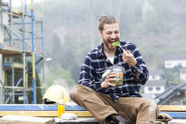 Construction worker eating salad while sitting outdoors at construction site - MJFKF00407