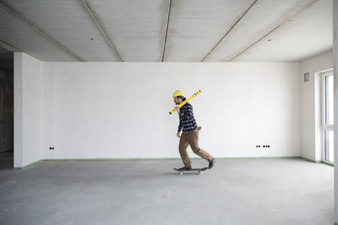 Young construction worker skateboarding in empty house - MJFKF00413