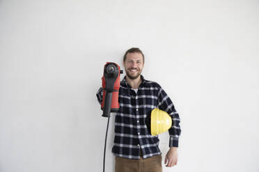 Smiling male worker holding work tool and helmet while standing against wall in house - MJFKF00416