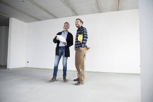Architect and construction worker looking away while standing against wall in empty house - MJFKF00419