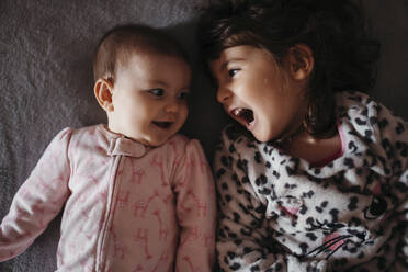 Girl screaming while looking at cute baby sister on bed - GEMF03918