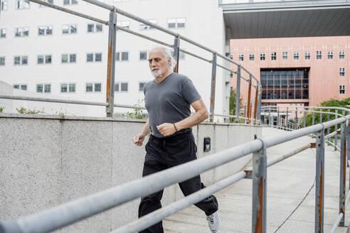 Senior man running on footbridge against buildings in city - MEUF01153