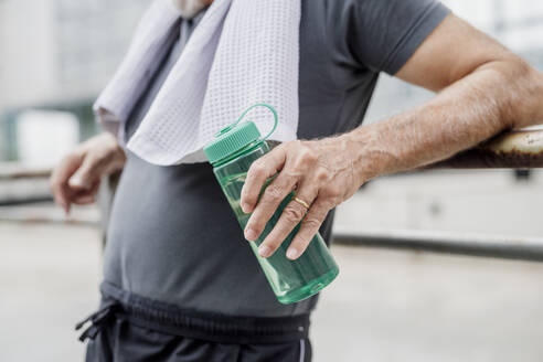 Close-up of senior man holding water bottle while standing in city - MEUF01174