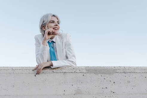 Smiling young woman wearing white suit standing by retaining wall against clear sky - TCEF00893