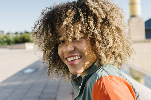 Happy young woman with curly hair during sunny day - XLGF00300