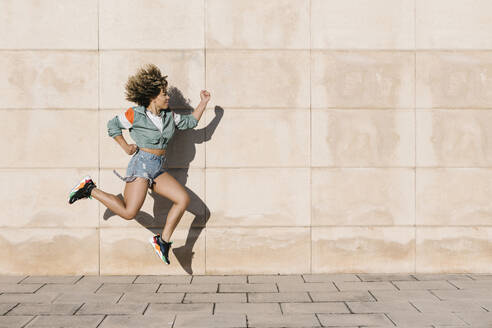 Young woman jumping against wall during sunny day - XLGF00309
