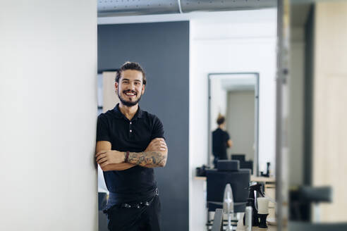 Confident male barber standing arms crossed in hair salon - SODF00809